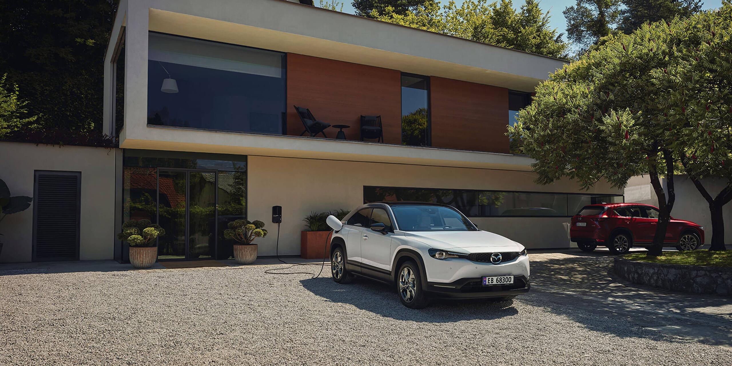 Mazda MX-30 tilkoblet lader på gårdsplassen foran et funkishus