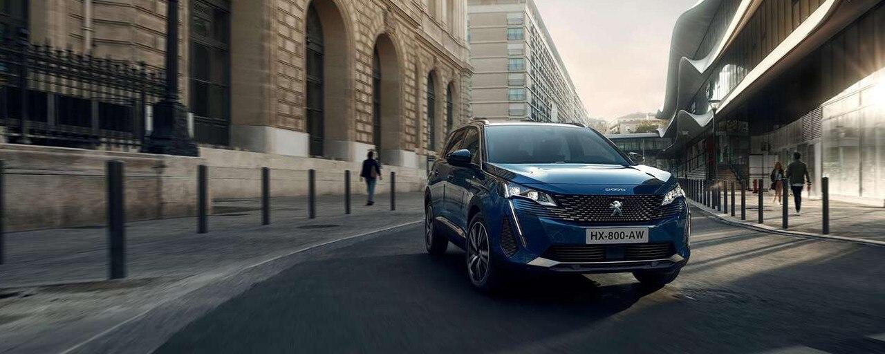 Blå Peugeot 5008 kjører på vei i byen