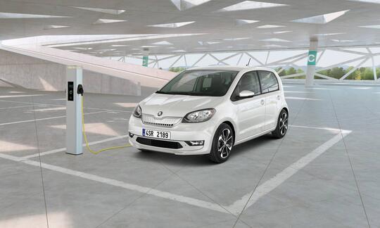 Hvit står parkert i parkeringshus tilkoblet lader