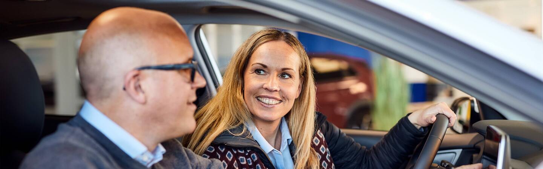 Mannlig selger og kvinnelig kunde i bilen
