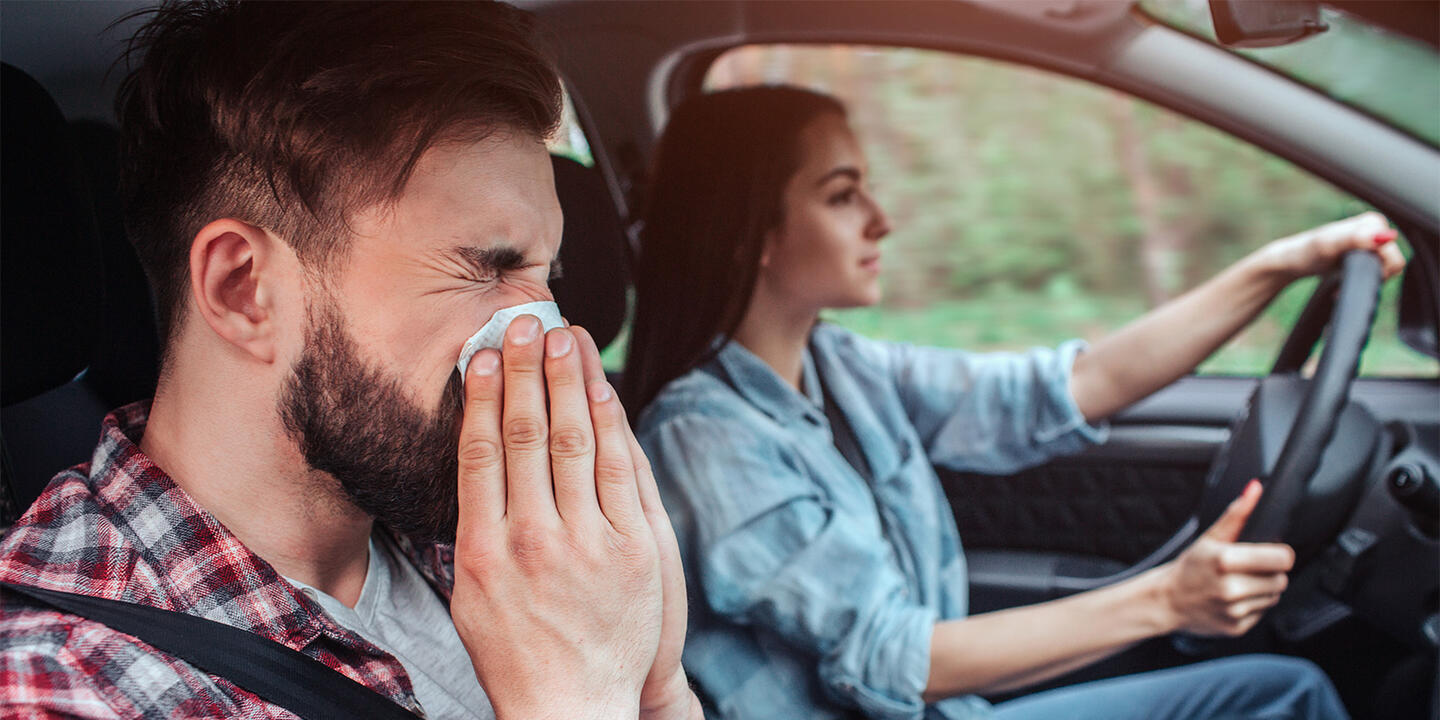 Man blowing his nose in car