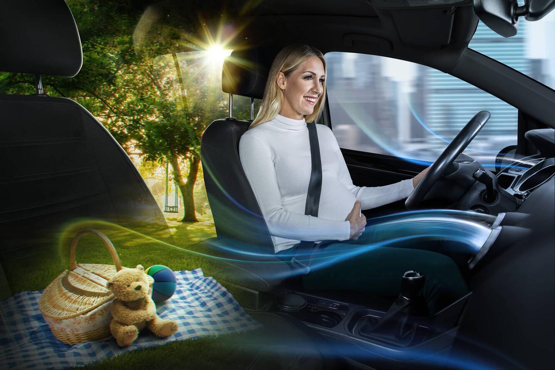 Blonde pregnant woman driving a car