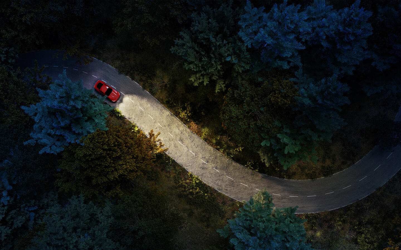 Bil lyser opp mørkt terreng