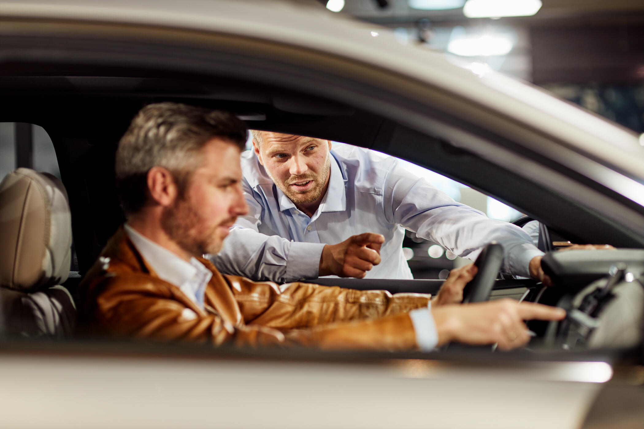 Customer test drives car with car salesman giving instructions